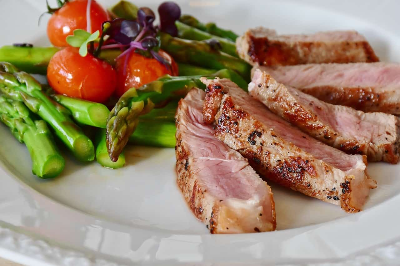 A plate with asparagus, veal, and tomatoes on it