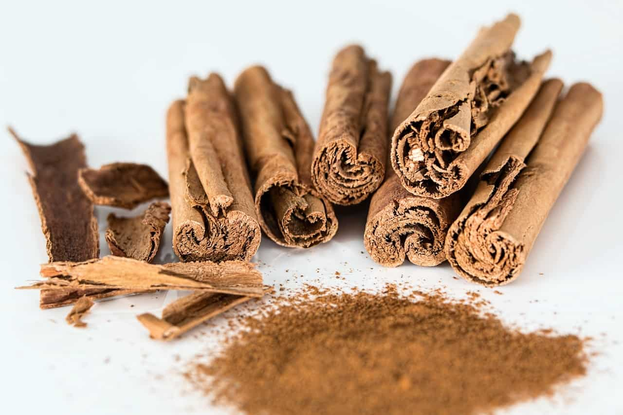 Cinnamon sticks next to a pile of cinnamon powder