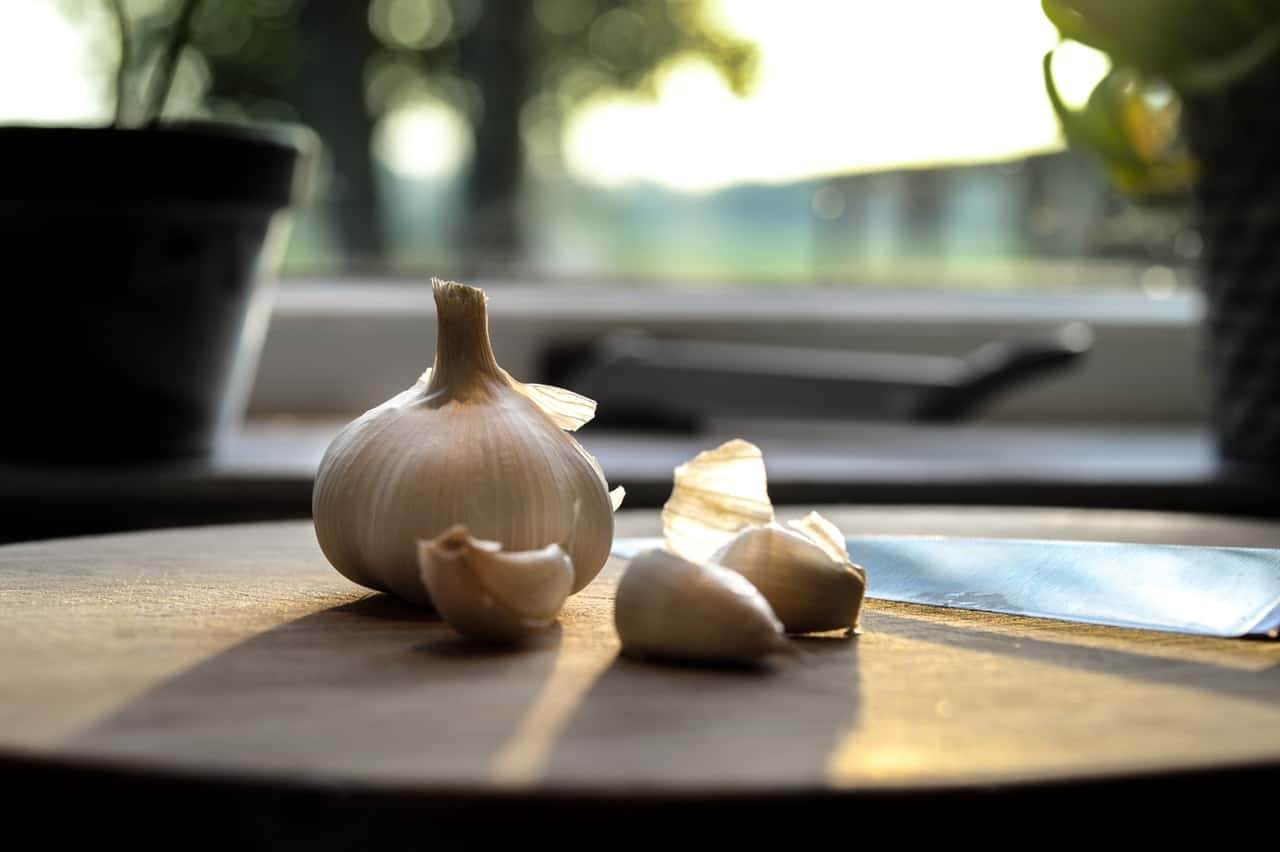 Garlic cloves on a chopping board next to a knife