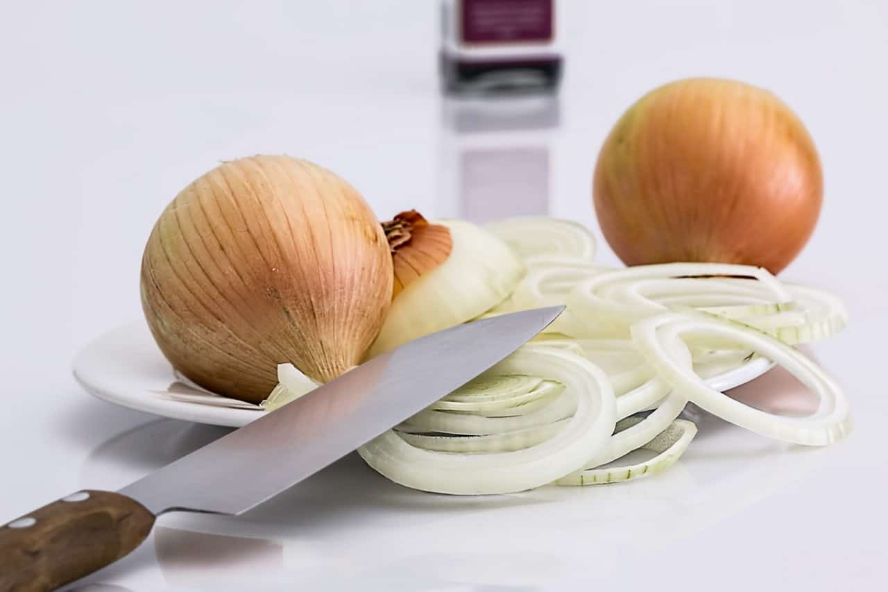 Sliced onions with a knife sitting on top