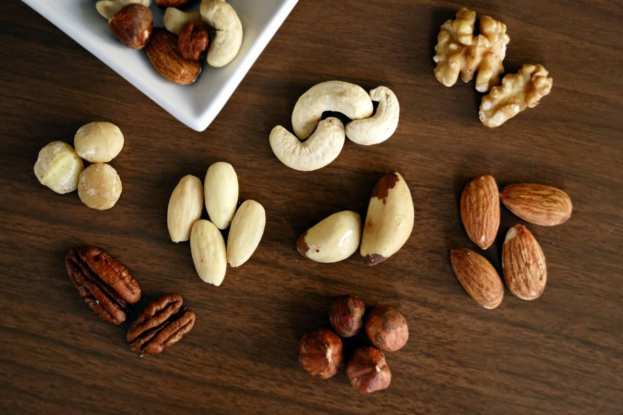 A table full of nuts such as almonds, cashews, pecans