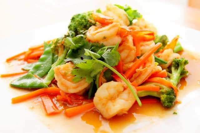 A seafood plate with prawns and broccoli