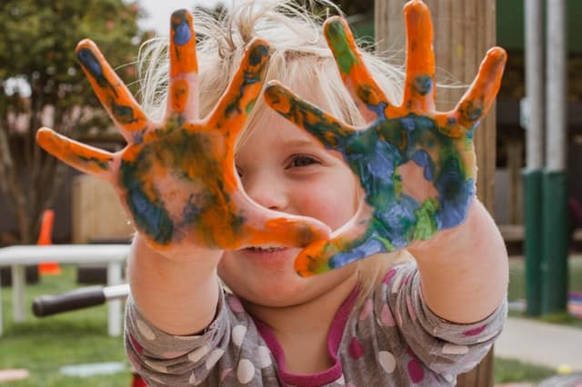 A child holding their painted hands up
