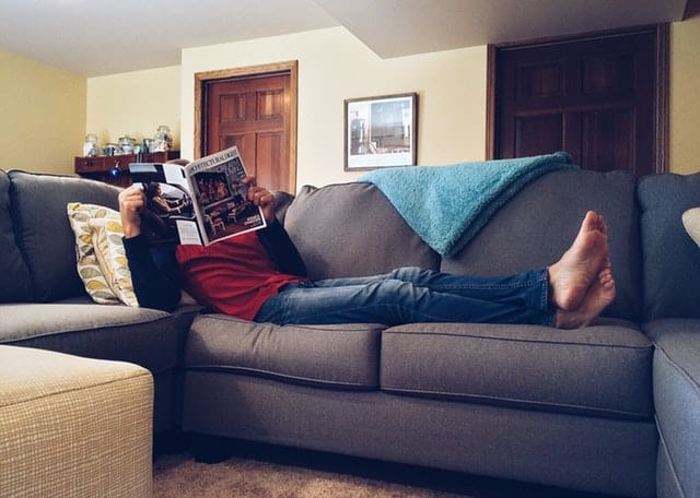 A person laying on a couch reading a magazine