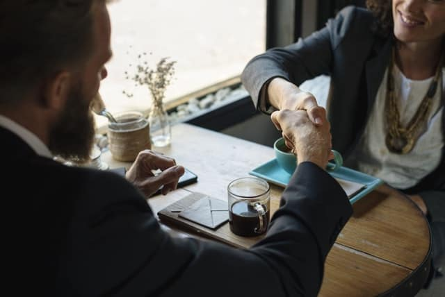 Two people at a business meeting shaking hands