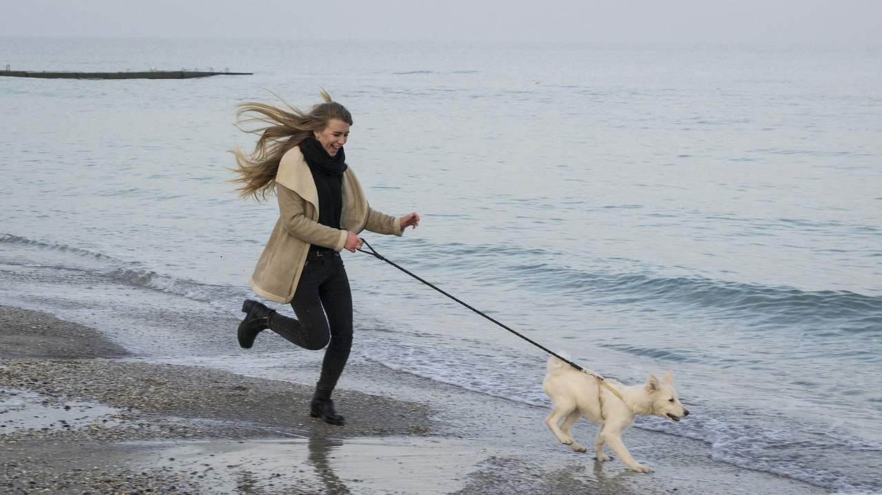 A woman running with a white dog on a beach on a cloudy day